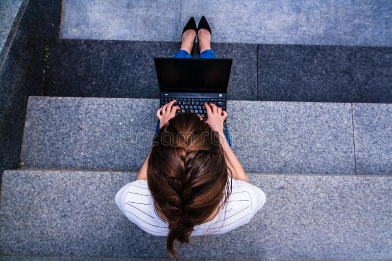 girl with notebook sitting on the gray steps stock image