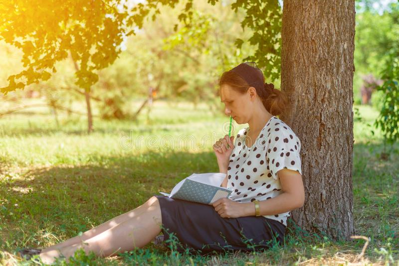 A girl with a notebook under a tree, thoughtfully holding a pencil near the lips stock photo