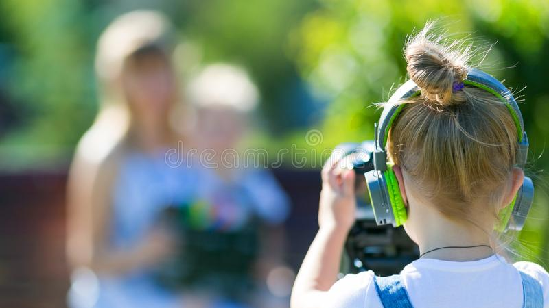Girl novice videoblogger shoots at the camera, defocus. The child makes his first videos on street in the city park royalty free stock photography