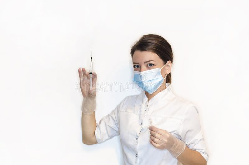 Girl nurse, young woman, lady doctor n white coat, sterile white latex gloves, mask holds syringe for injection, vaccination, pain royalty free stock photography