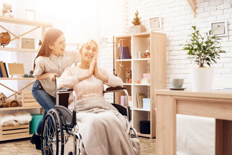 Girl is nursing elderly woman at home. Girl is riding woman in wheelchair. Woman is enjoying herself. royalty free stock photography