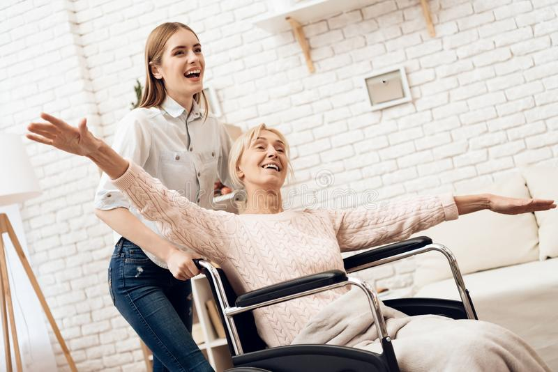 Girl is nursing elderly woman at home. Girl is riding woman in wheelchair. Woman feels like flying. royalty free stock images