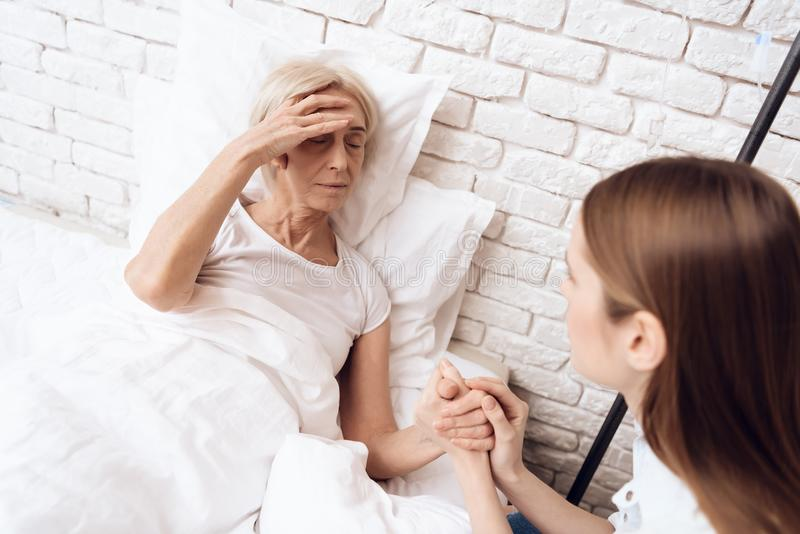 Girl is nursing elderly woman at home. They are holding hands. Woman is feeling bad. royalty free stock images