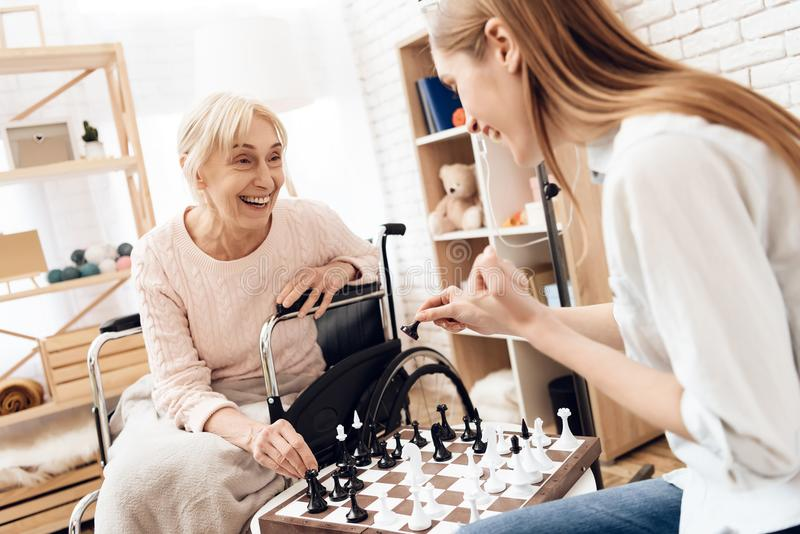 Girl is nursing elderly woman at home. They are playing chess. royalty free stock image