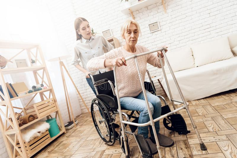 Girl is nursing elderly woman at home. Woman is trying to stand up from wheelchair. royalty free stock image
