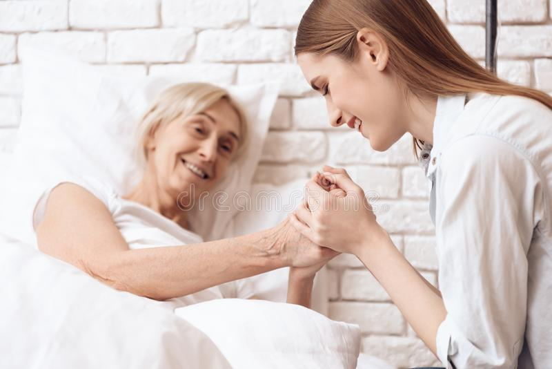 Girl is nursing elderly woman at home. They are holding hands, happy. royalty free stock photos