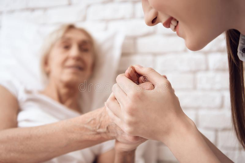 Girl is nursing elderly woman at home. They are holding hands, happy. stock images