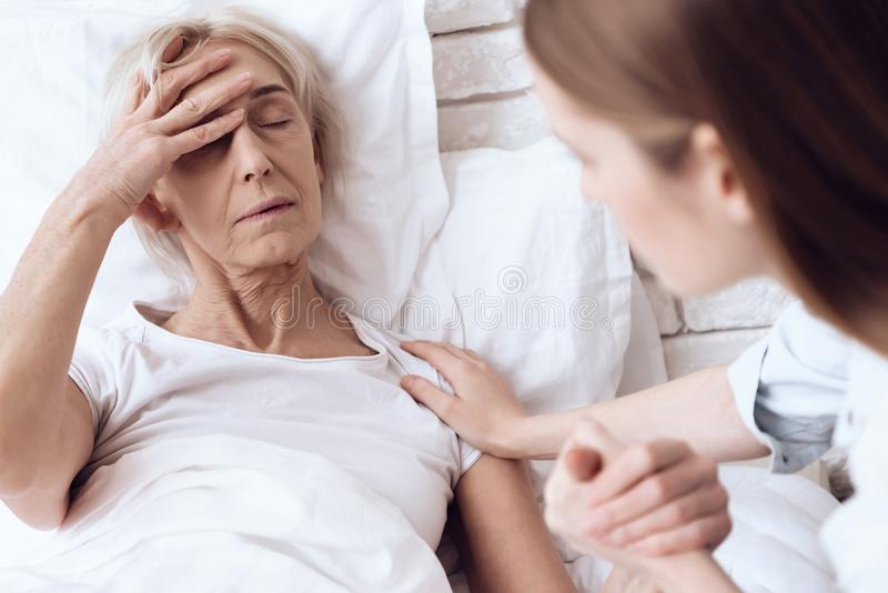 Girl is nursing elderly woman at home. They are holding hands. Woman is feeling bad. stock image