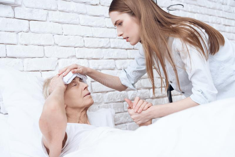Girl is nursing elderly woman at home. They are holding hands. Woman has compress on her head. royalty free stock photos