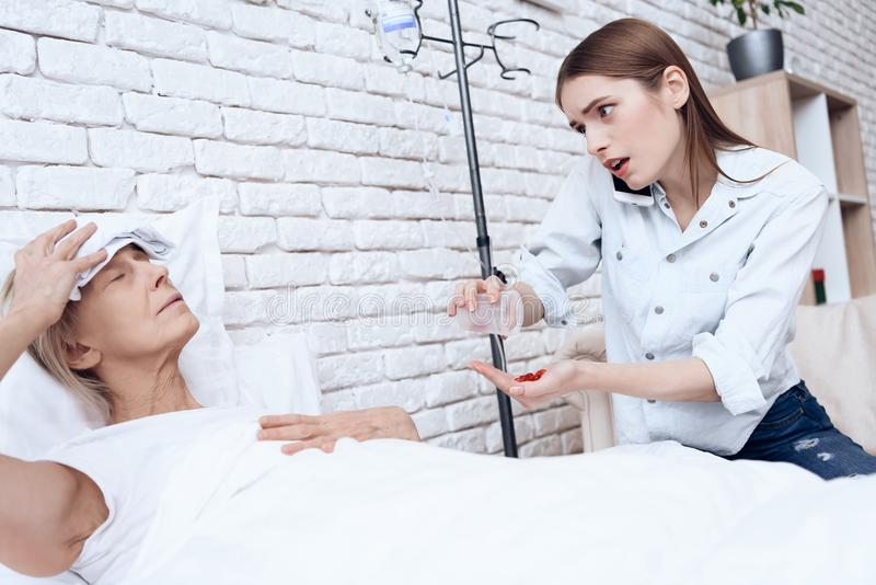 Girl is nursing elderly woman at home. Girl is on phone, giving pills to woman. royalty free stock photos