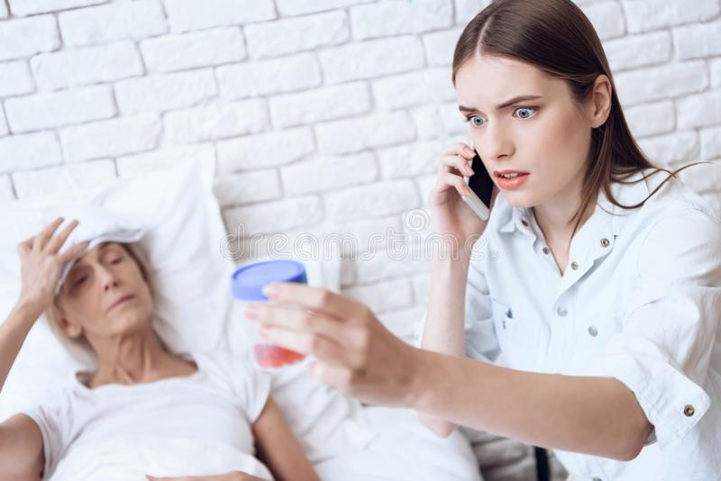 Girl is nursing elderly woman at home. Girl is on phone, giving pills to woman. royalty free stock photo