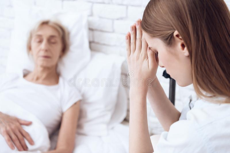 Girl is nursing elderly woman at home. Woman is feeling bad, girl is praying. royalty free stock photos