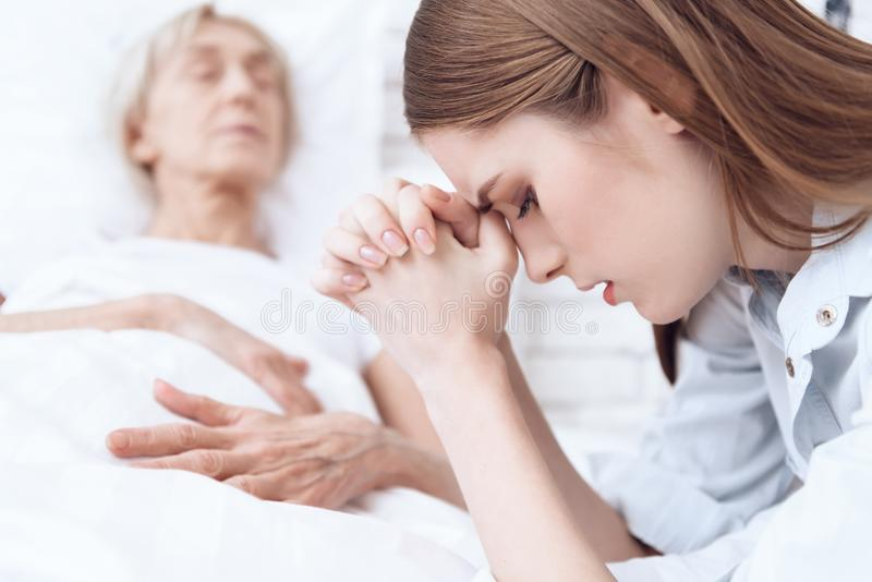 Girl is nursing elderly woman at home. Woman is feeling bad, girl is praying. stock photography