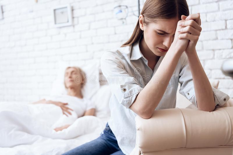 Girl is nursing elderly woman at home. Woman is feeling bad, girl is worried. stock photo