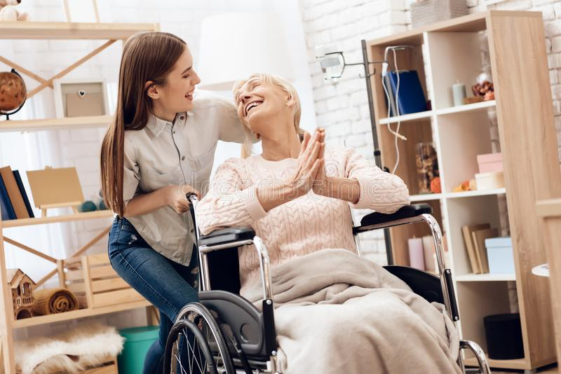 Girl is nursing elderly woman at home. Girl is riding woman in wheelchair. Woman is enjoying herself. stock image