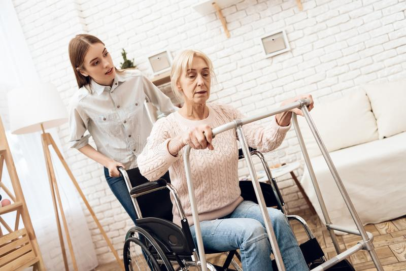Girl is nursing elderly woman at home. Woman is trying to stand up from wheelchair. stock photo