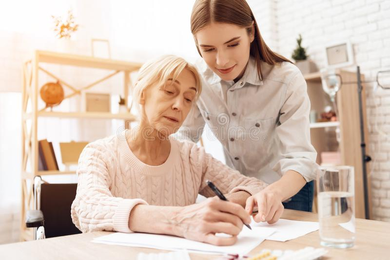 Girl is nursing elderly woman at home. Girl is helping woman write. royalty free stock photo