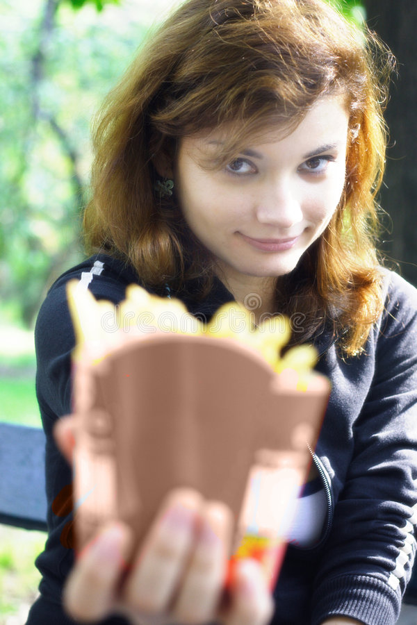 Girl offering french fries. Pretty girl with french fries in her hand royalty free stock photo