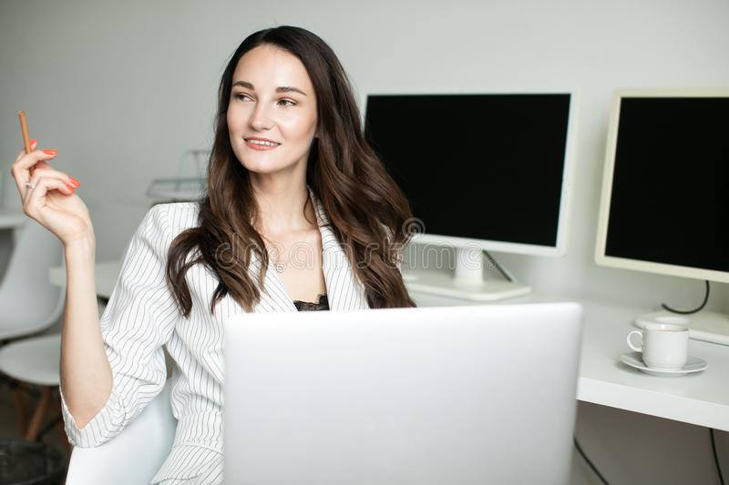 Girl in the office holding a laptop royalty free stock images