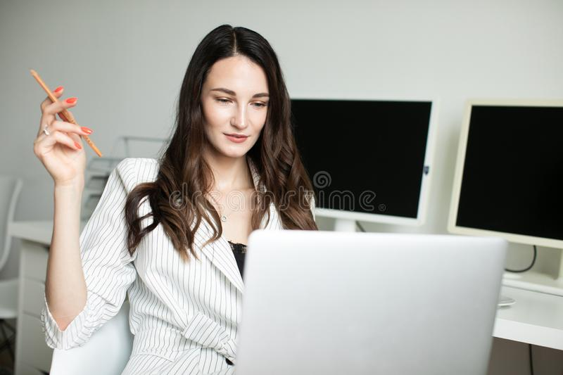 Girl in the office holding a laptop stock photo