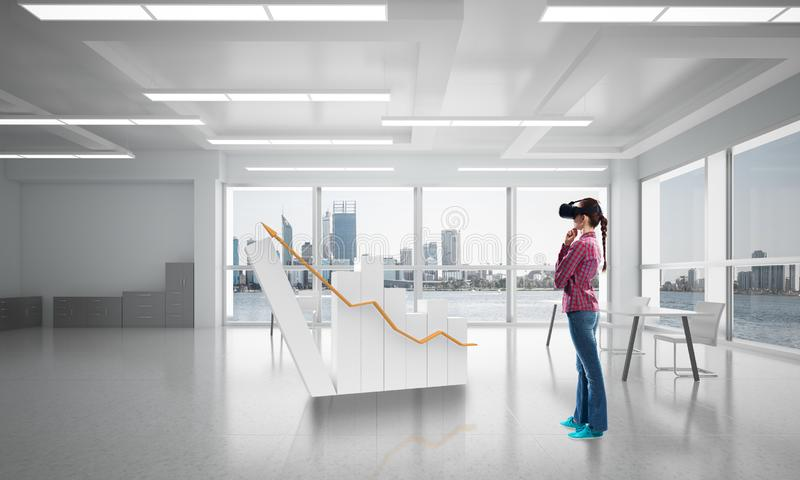 Girl in office interior in virtual reality mask using innovative technologies. Mixed media stock photo