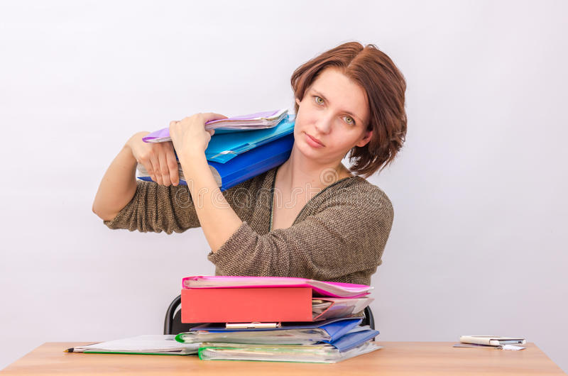 Girl office staff loads the stack of folders royalty free stock images