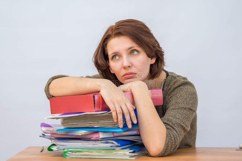 Girl office staff thoughtfully leaning on a stack of folders stock photo