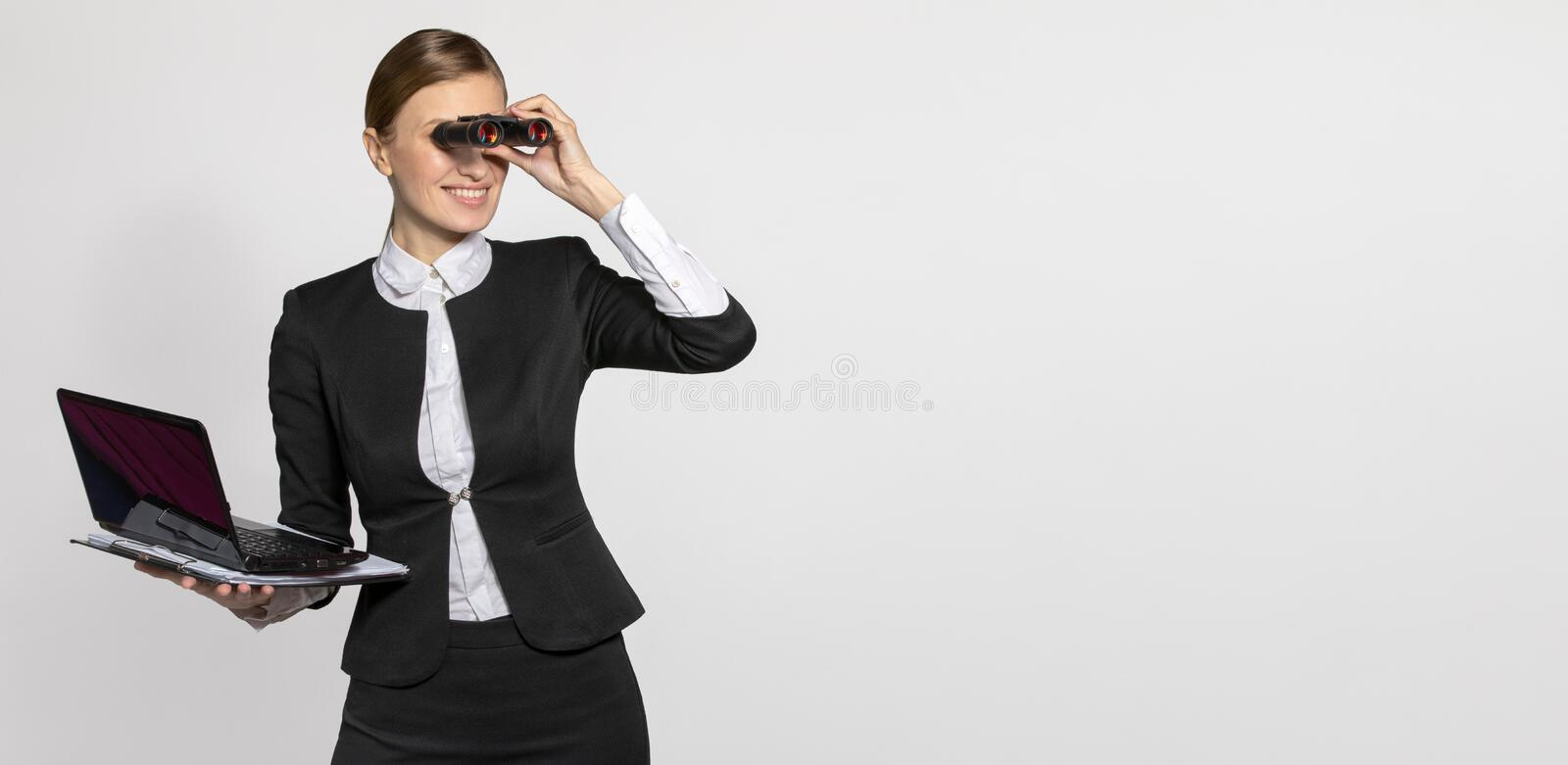 Girl in office suit looking through binoculars. Businesswoman with a laptop and tablet in his hands looking through binoculars to the side. The concept of the stock photos