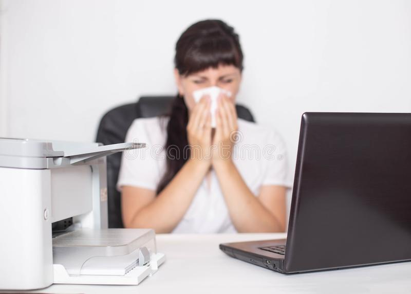 Girl office worker sits at a computer in the office and blows her nose the concept of allergies to dry and humid air as well as. Dust in the room, office stock images