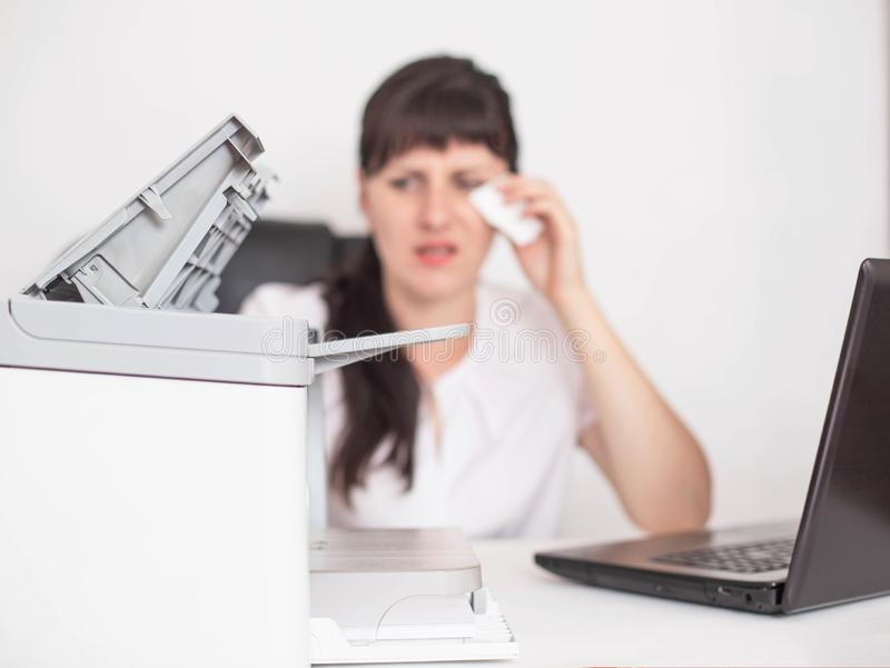 Girl office worker sits wiping tears out of her eyes the concept of office allergies to office equipment and air conditioning,. Health problems, nasopharynx royalty free stock photos