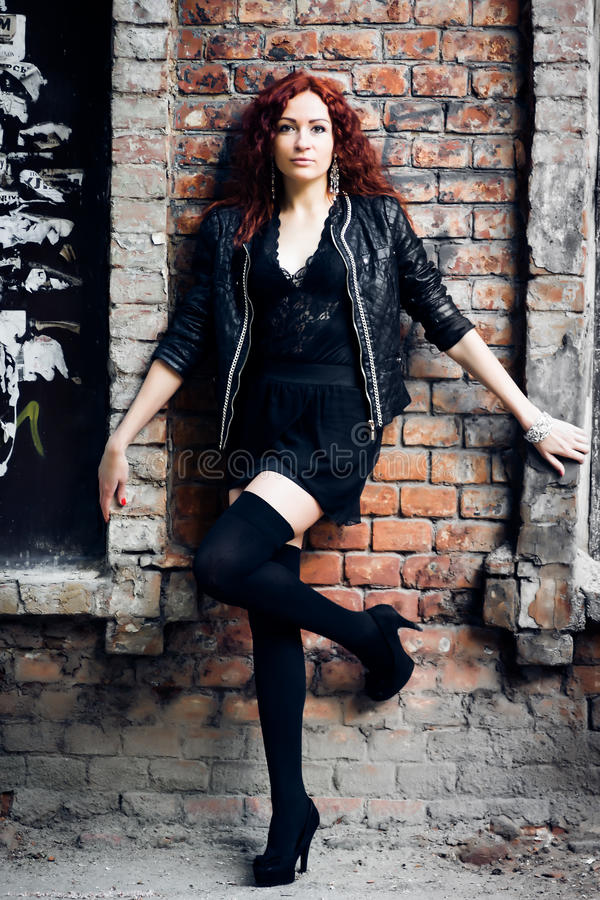 Girl on the old red brick wall. Fashion girl with red hair stands leaning against a old red brick wall background royalty free stock photography