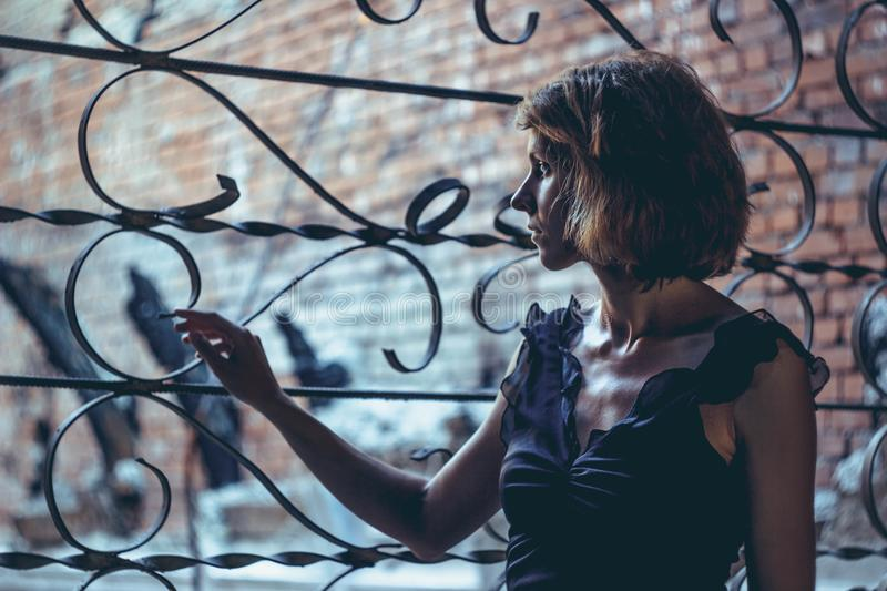 The girl at lattice Windows. The girl in the old ruined house in the ward royalty free stock image