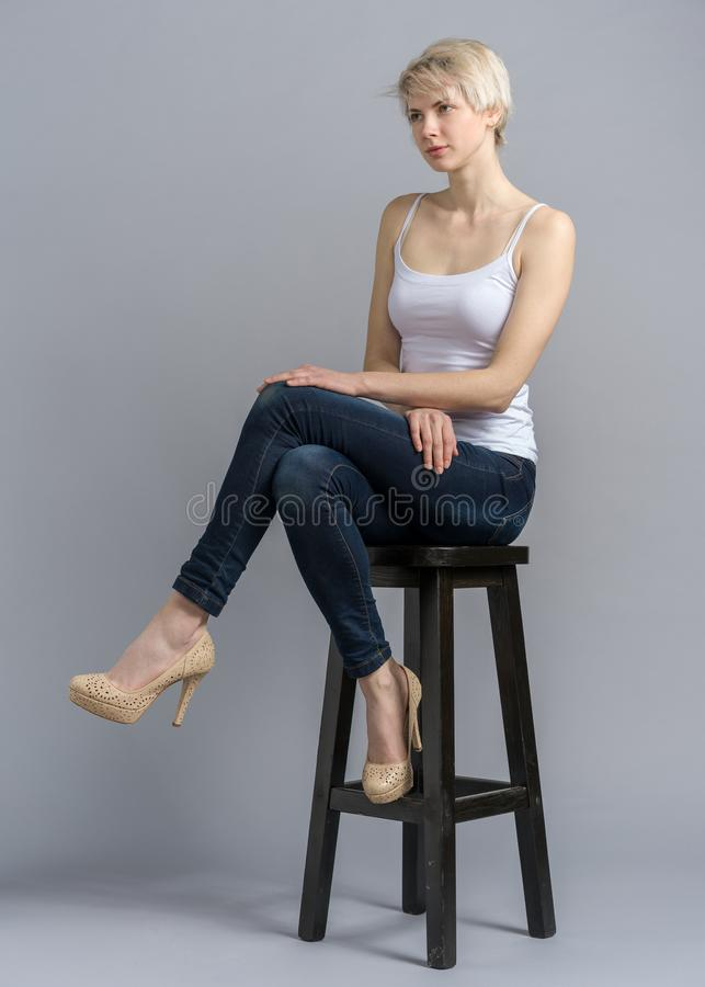 Free Girl On Chair With Crossed Legs And Serious Face Stock Photos - 139527133