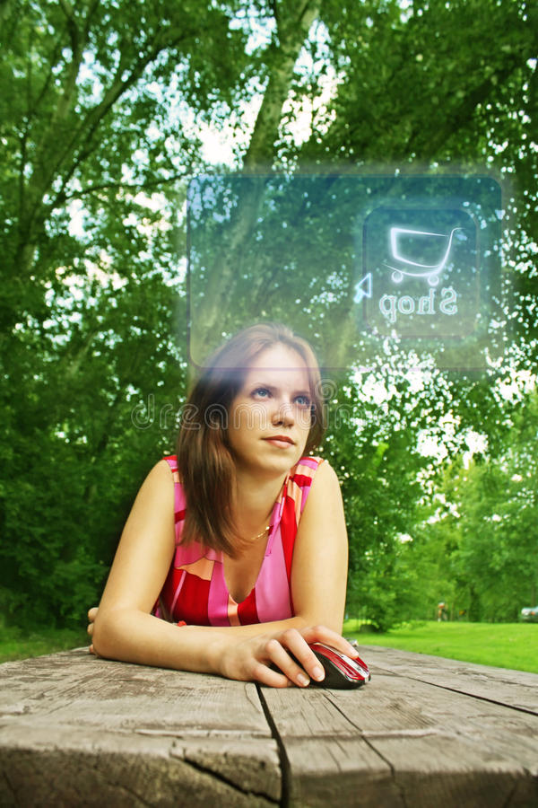 Girl online in park. Young woman buying on-line with modern technology at a wooden table in a park