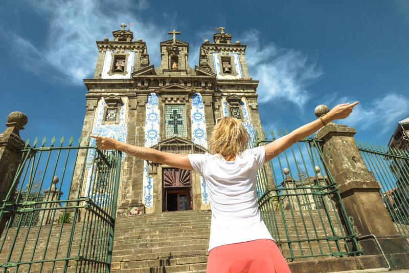 Saint Ildefonso church enjoying. Girl with open arms in front of azulejo facade of Saint Ildefonso church. The Igreja de Santo Ildefonso is an eighteenth-century stock photos