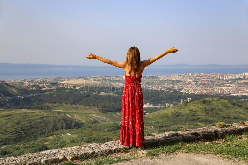 A girl with open arms stands on the edge of a cliff stock photo