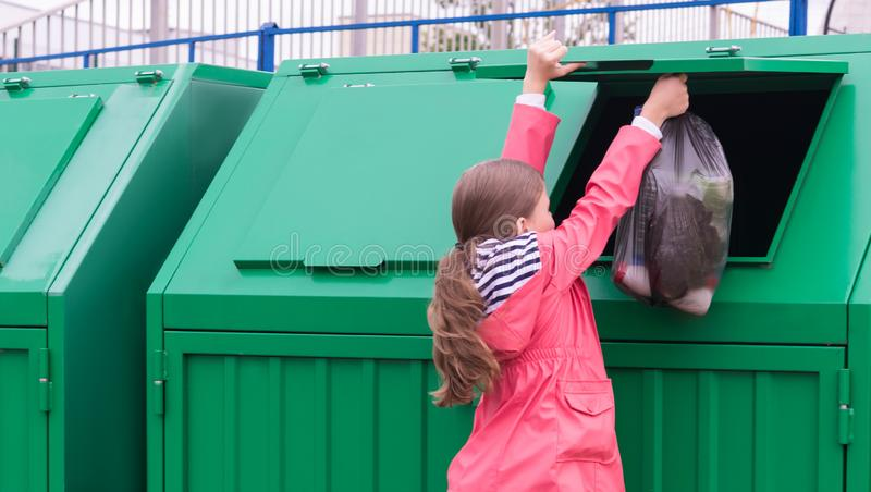 The girl opened the dumpster to vibrate the waste bag stock image