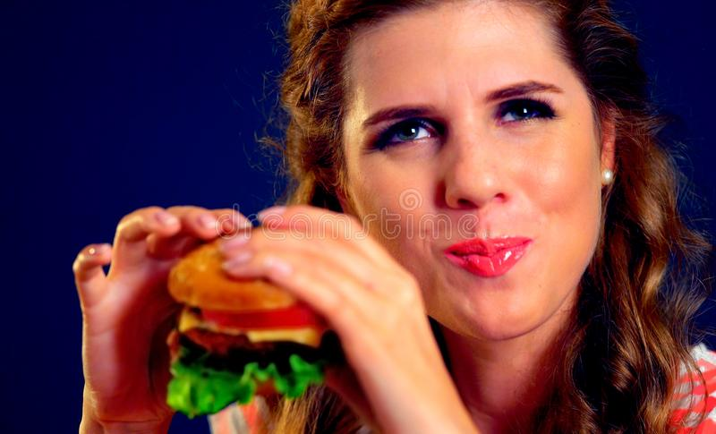 Girl opened her mouth, holding a hamburger on his outstretched hands and closed her eyes. Woman eating sandwich. Girl with pleasure eats burger after diet. She stock image