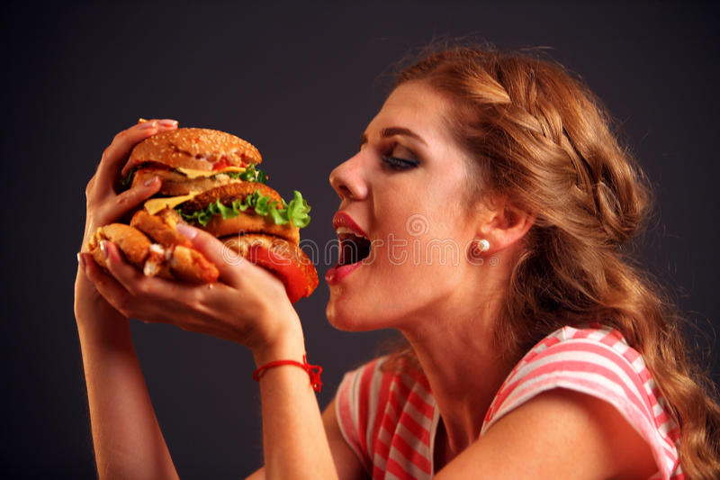 Girl opened her mouth, holding a hamburger on his outstretched hands and closed her eyes. Woman eating sandwich. Girl with pleasure eats burger after diet. She stock photos