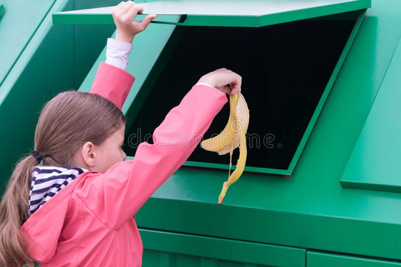 The girl opened the trash tank and throws out the skin of a banana royalty free stock image