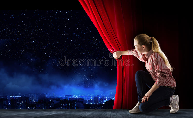 Girl opening curtain. Young woman in casual opening drape curtain stock photo