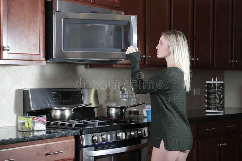 Girl opening door of microwave cooker. Blond teenage girl wearing only dark top (without pants) in the kitchen opening the door of a microwave oven royalty free stock image