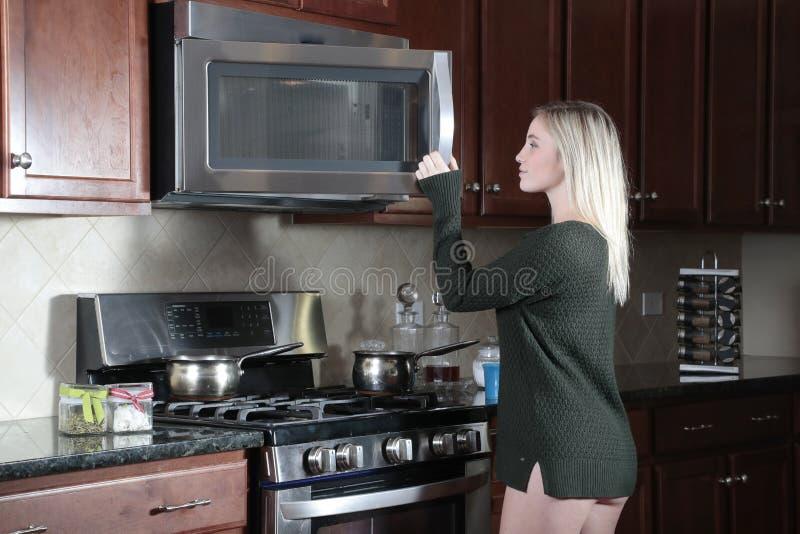Girl opening door of microwave cooker royalty free stock image