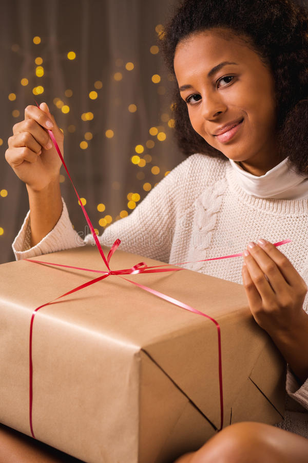 Girl opening xmas present. Vertical view of girl opening xmas present stock photo