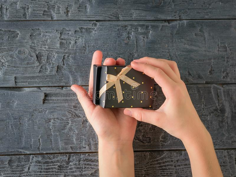 The girl opens a black box with a surprise on a black wooden table. The view from the top stock photos