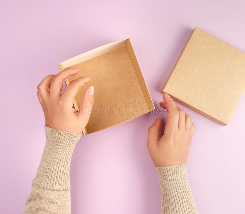 Girl opens a brown square box on a purple background. Top view, concept of giving gifts royalty free stock images