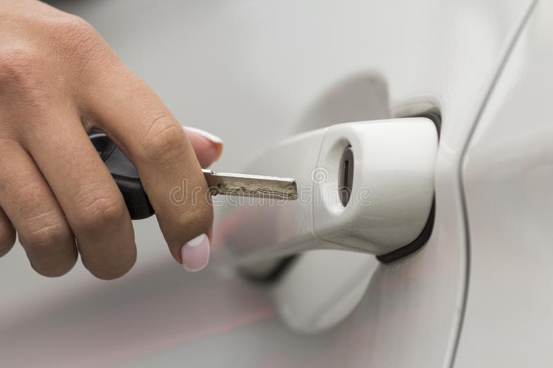 The girl opens the car. Arm girls opens key door white passenger car closeup royalty free stock photo