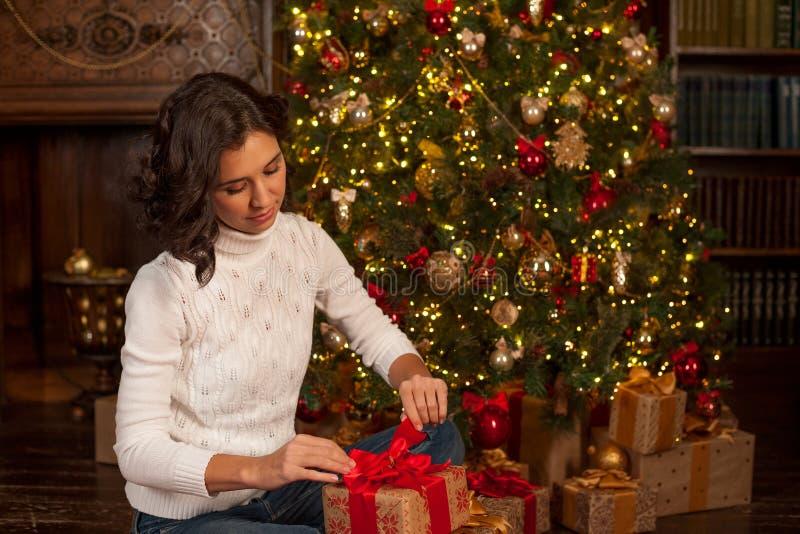 Girl opens Christmas gift royalty free stock image