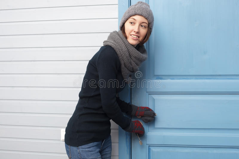 Girl opens door with keys. Looking aside royalty free stock images