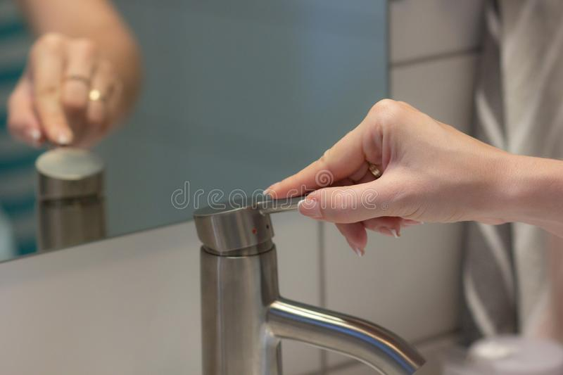 The girl opens the faucet for washing hands, in the mirror reflected her hand royalty free stock photo